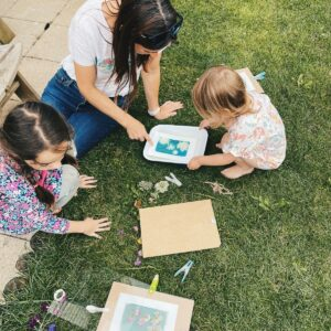Mum and daughters sitting on the grass using their cyanotype papers in the summer sun, with flowers.