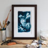 A framed seaweed cyanotype print sat on a wooden shelf surrounded by shells and other items from the beach